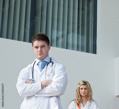 Two doctors with a hospital in the background
