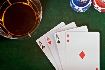 4 aces lying next to playing chips and drink.