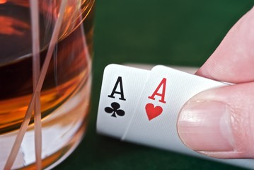 Showing two aces next to a whisky glass.