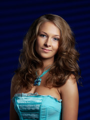 Portrait of the young girl in a blue corset on a dark blue backg