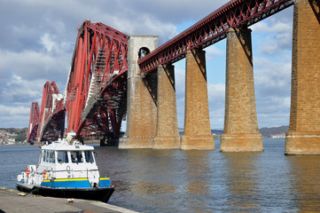 ferry beside the forth railway bridge in scotland