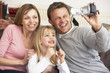 Parents And Daughter With Video Camera