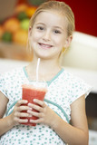 Young Girl Drinking A Berry Smoothie