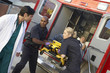 Paramedics and doctor unloading patient from ambulance - 12969654
