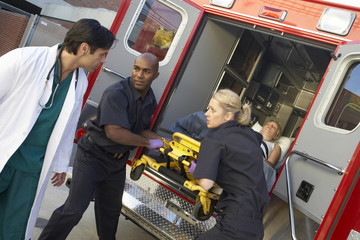 Paramedics and doctor unloading patient from ambulance