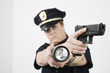 Police woman pointing handgun and holding flashlight.