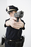 View of a police woman aiming with pistol.