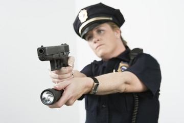 Police woman pointing handgun and holding flashlight.