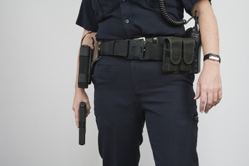 Police woman holding a loaded pistol ready to fire.