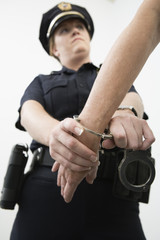 Close up of a person being hand cuffed by a police woman.