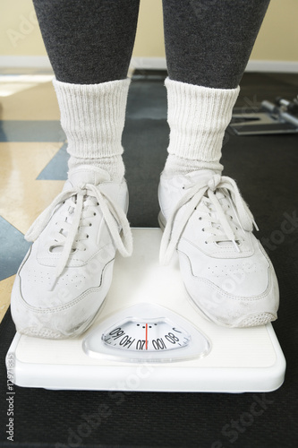 Senior woman standing on weighing machine.