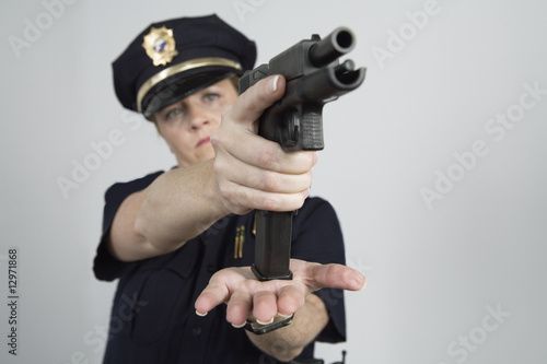Police woman loading a pistol.