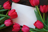 White envelope surrounded by tulips