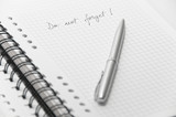 Remembering note on white notebook with elegant silver pen