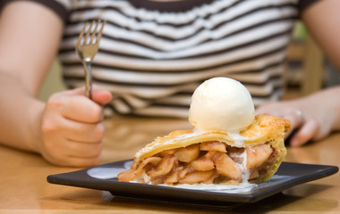 Woman holding up fork, ready to eat apple pie a la mode