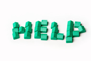 Model plastic houses/homes forming the word HELP.