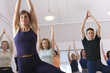 Teacher guides student in yoga class - 13027259