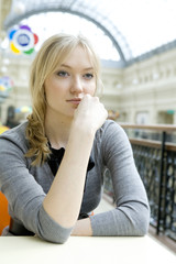 young attractive blond pensive woman sitting at table in cafe in