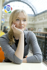 young attractive blond woman sitting at table in cafe in state d