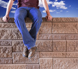 Man sitting on a brick wall