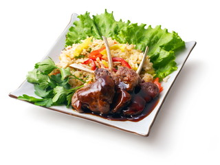 Fried meat ribs in sauce with rice salad and parsley
