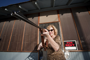 Woman on front proch with rifle