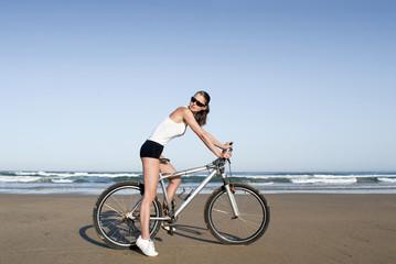 Frau mit Fahrrad am Strand