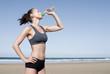 Sportliche junge Frau trinkt am Strand