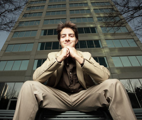 Man sitting with a building in the background