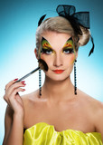 Beautiful woman with creative face-art and make-up brush
