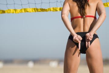 Junge Frau spielt Volleyball am Strand