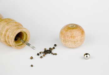 Peppermill and black pepper isolated in white
