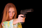 Attractive girl aiming with gun on black background
