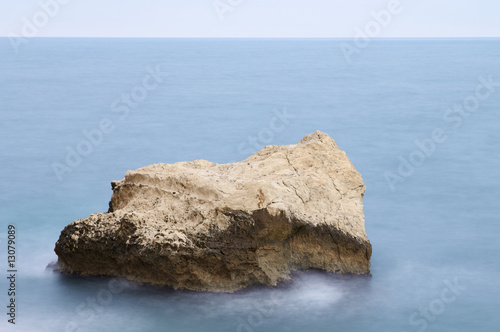 Rock in calm sea with blue sky