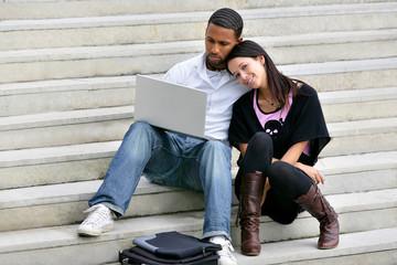 couple assis sur les marches avec ordinateur portable