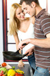 Young attractive happy smiling couple playfully cooking
