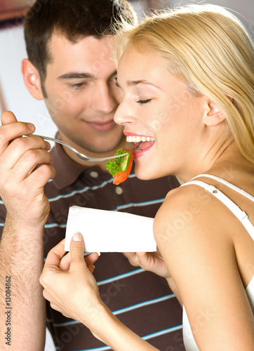 Young happy smiling couple eating playfully vegetable