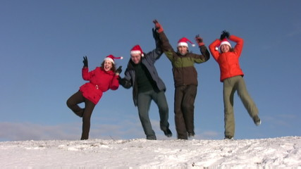dancing friends with christmas hats on snow