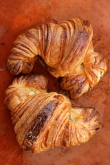 Two croissant pastries over orange clay