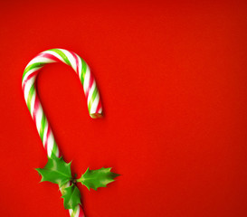 Candy cane with pretty holly leaves red background, candy cane