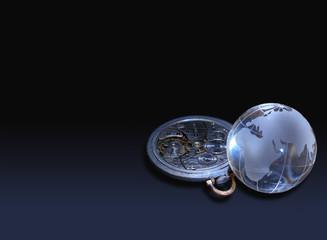 Glassy globe with old watch mechanism lying on dark