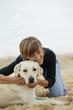 femme souriante caressant un Labrador au bord de la plage