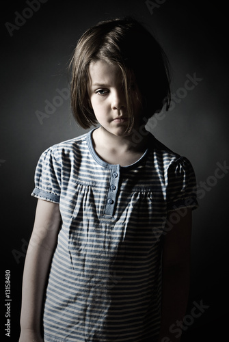 Low Key Shot of a Sad Little Girl against Grey Background