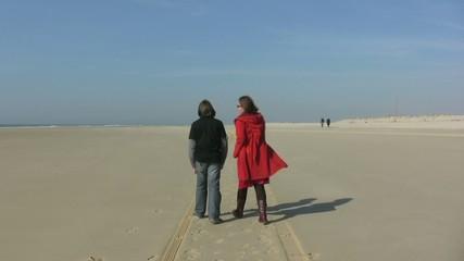 mère et fils discutant sur la plage de dos