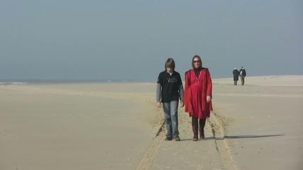 mère et fils se promenant sur la plage