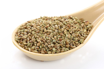 Spoon of ajwain seeds on white background