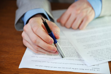 A businessman signs papers.