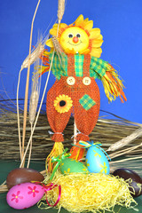 Springtime: ornamental scarecrow, hay, spikes and eggs