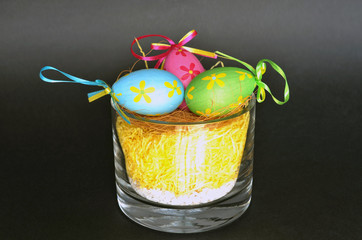 Glass cup with straw and decorative Easter eggs on black