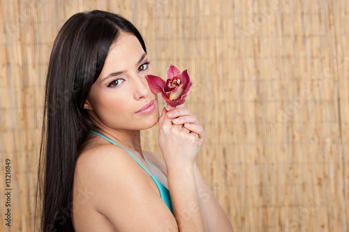 Pretty woman with orchid in front of reed, lots of copy space